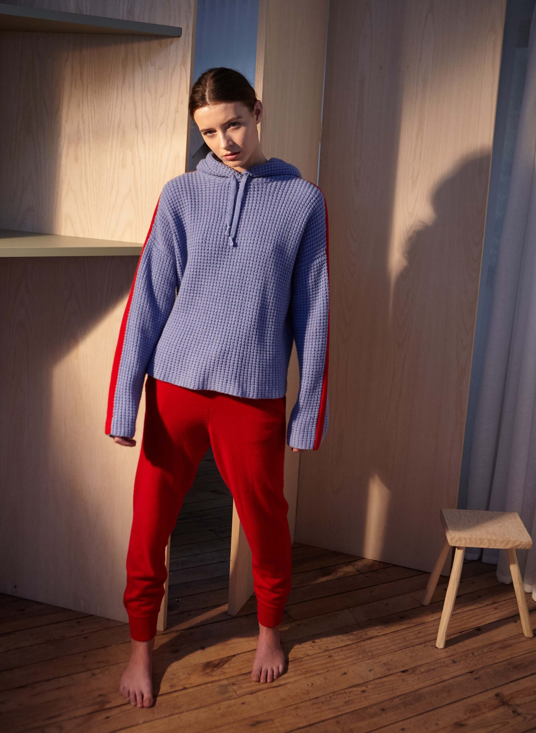 Model wearing purple sweatshirt and red track pants
