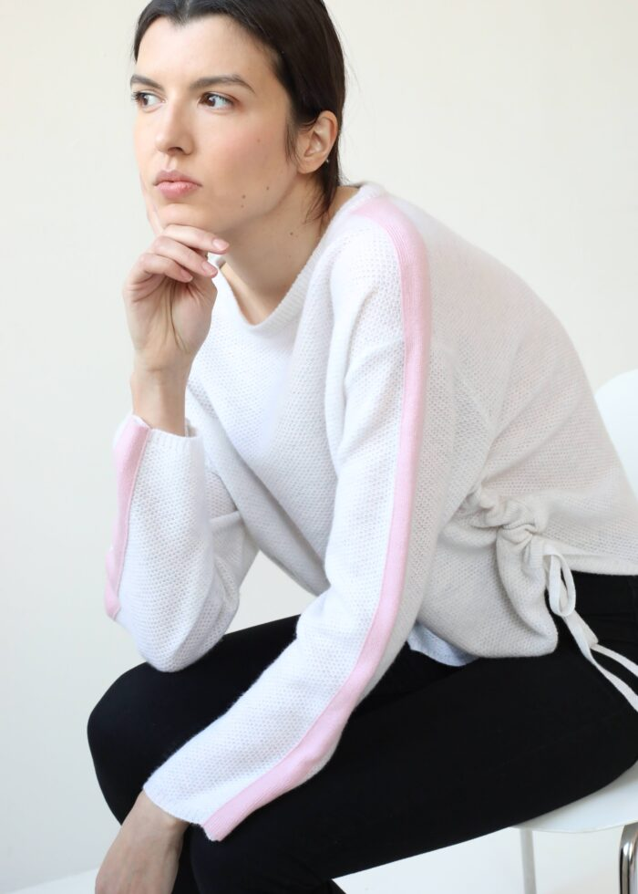Girl wearing white cashmere sweater with pink stripe on sleeves